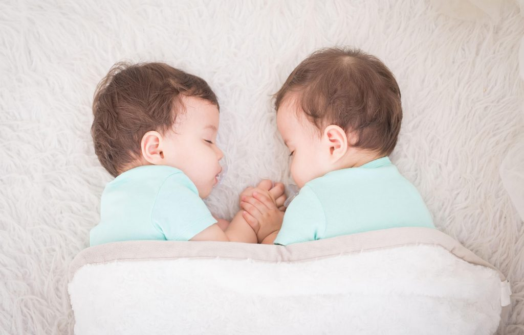 Physical touch and cuddling is a good way to build a bond between twins.