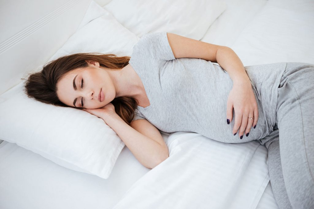 Side view of sleeping pregnant woman on bed