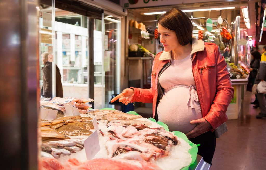 Woman buying the right seafood during pregnancy.