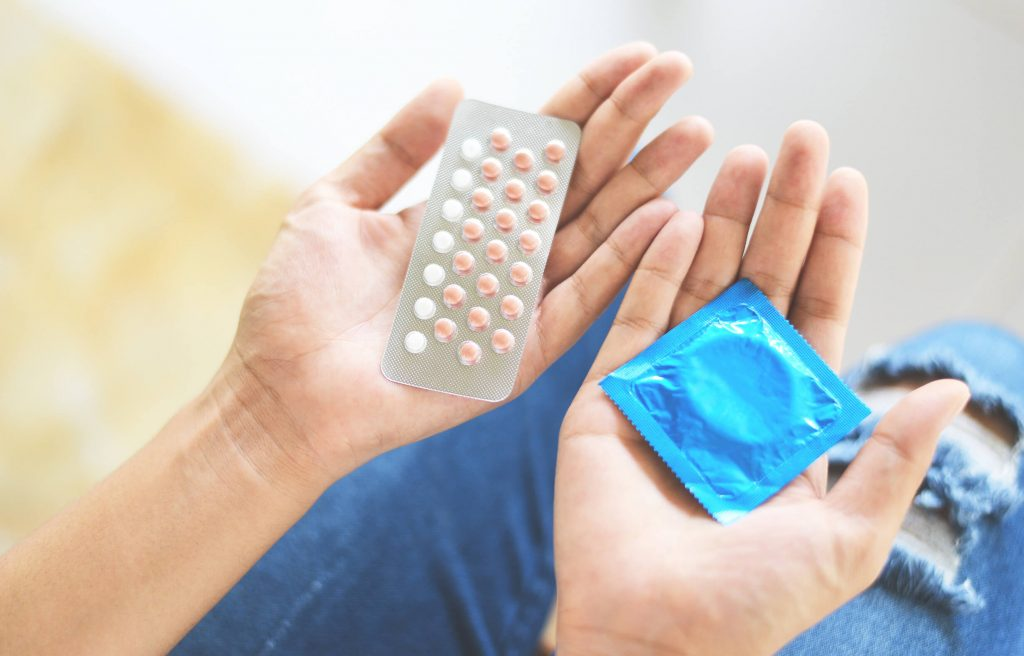 Woman holding contraception methods to prevent unplanned pregnancy