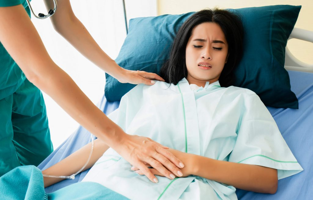 Doctor helping woman with upper stomach pain during pregnancy