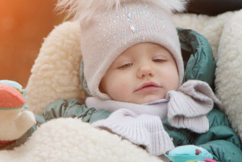 Baby covered in warm clothes showcasing winter care for babies